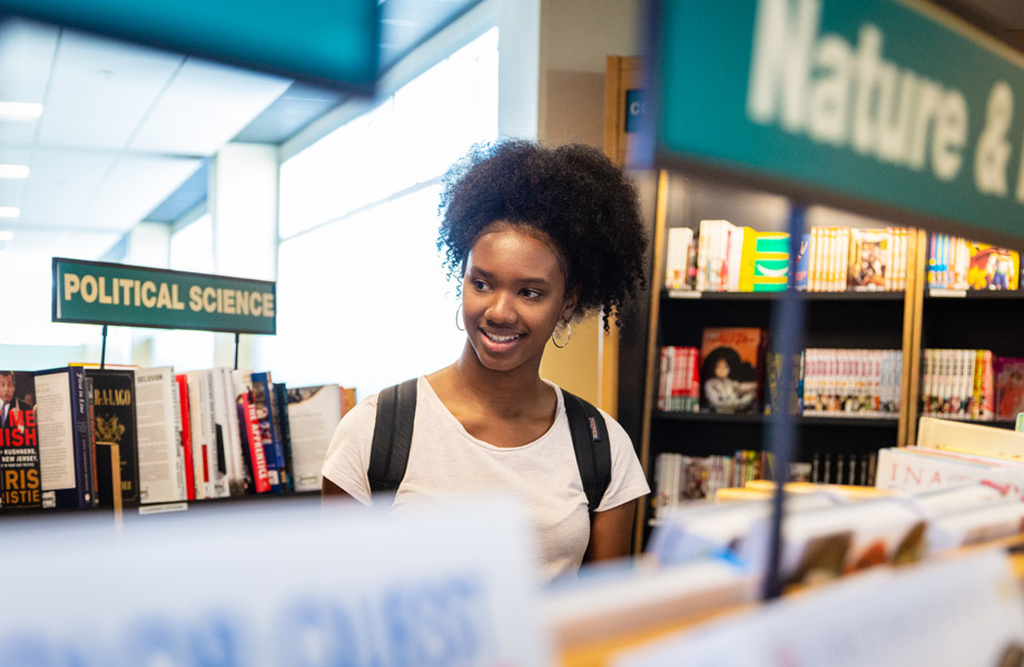 Young woman browsing bookshelves at Tampa campus bookstore