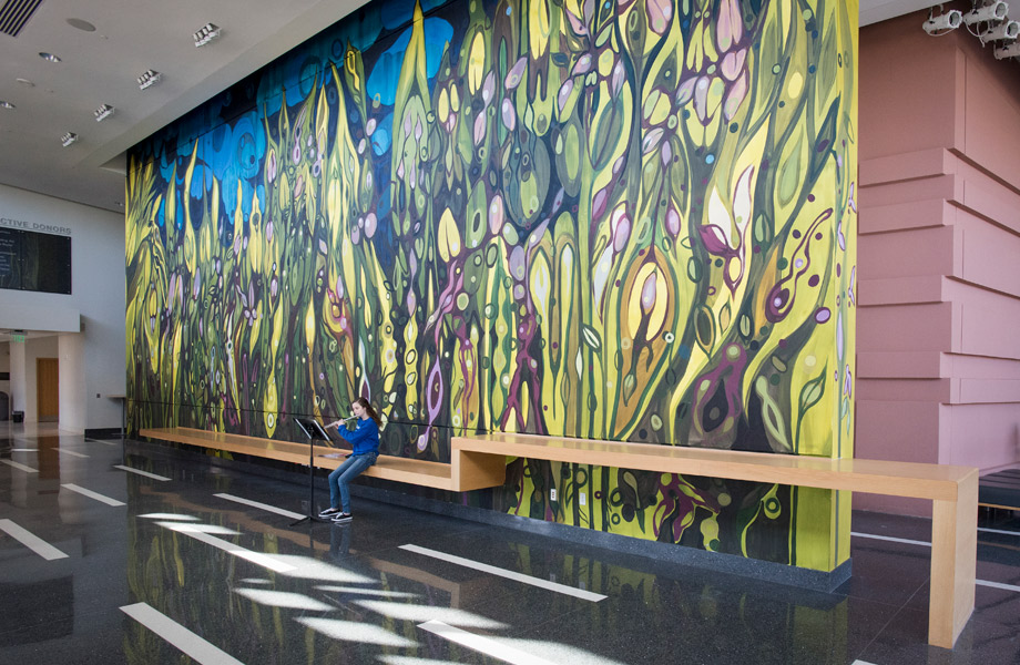 A student playing an instrument in the lobby of Music building, in front of mural