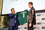 Muma College of Business Dean giving a jersey to their newest donor