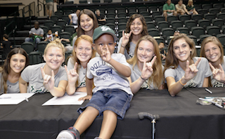 """Attendees of Fan Fest pose with the """"Go Bulls!"""" hand symbol"""