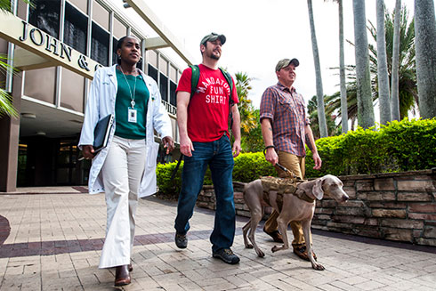 Two veterans and a service dog on campus with a staff member