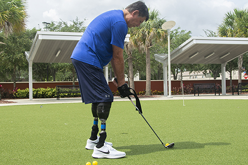 Local veteran Rufus Myers testing the prosthetic device on a putting green at Tampa's V.A. The device, developed by USF students in collaboration with the V.A., allows Myers the ability to golf again.