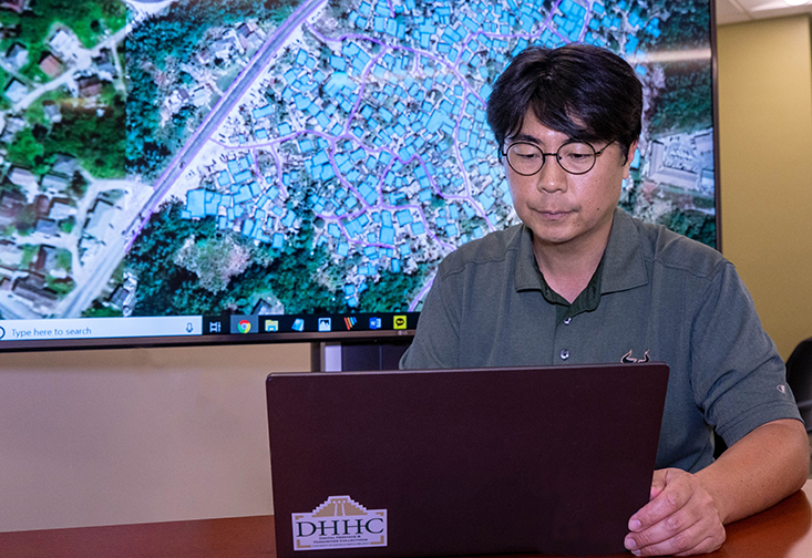 USF graduate student Kyutae Ahn looking at data maps of homes in the Bahamas