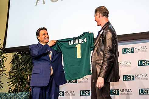 Muma College of Business Dean Moez Limayem presenting KnowBe4 CEO Stu Sjouwerman with a USF Jersey.