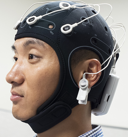 A research participating wearing a brain wave monitoring device