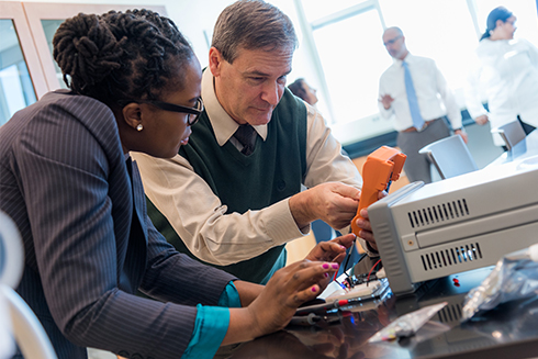 Dr. Robert Frisina and faculty member experimenting with medical engineering device