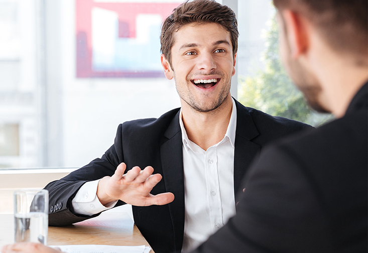 A stock photo of a man smiling in a job interview.