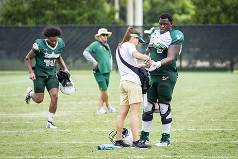 A USF-athletics trainer with a USF Football player