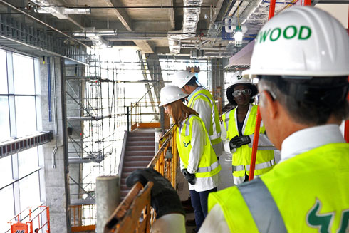 Dr. Lockwood and USF Health staff wear hard hats and vests inside the construction site at Water Street.
