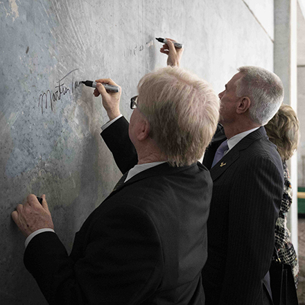 USF President, Steve C. Currall and Martin Tadlock sign the wall with their names.
