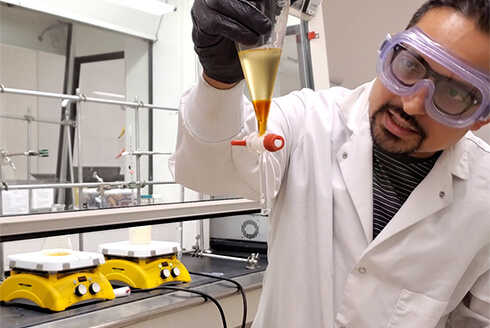 "USF graduate assistant runs a chemistry experiment while recording a video to share with students during the COVID-19 ""stay at home"" mandate."