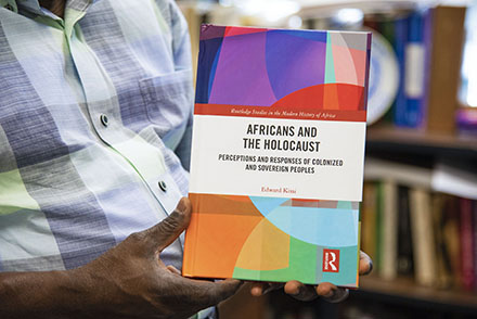 Dr. Kissi holds his new book