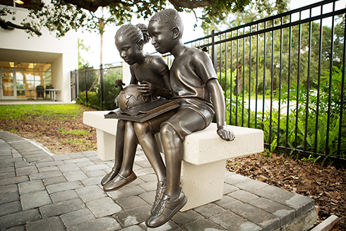 A sculpture featuring two African American children engrossed in a book at Tampa's C. Blythe Andrews Jr. Public Library