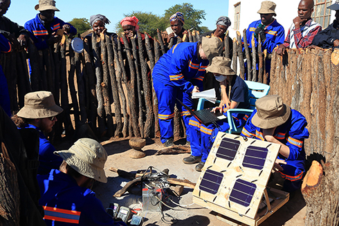 People working on portable solar energy devices in Africa