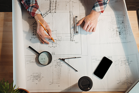 An overhead photo of someone working on schematic drawings