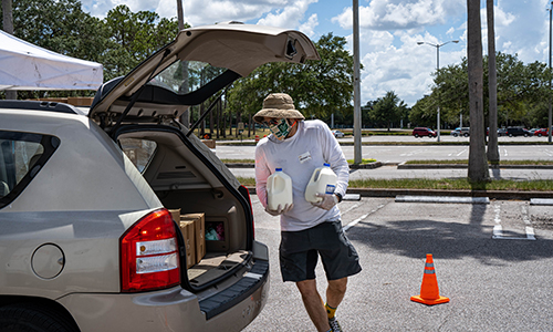 USF volunteer loading milk into a vehicle