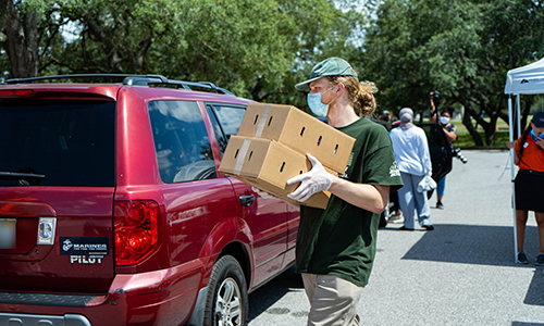 USF volunteer loading food into a vehicle