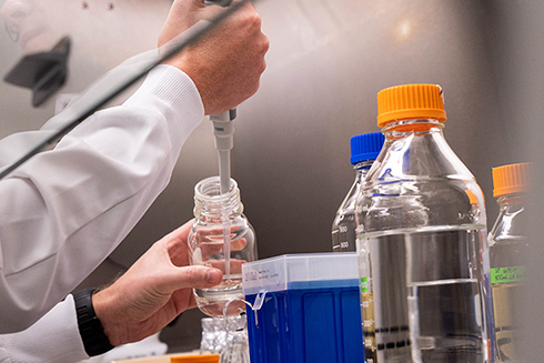 A stock photograph of a researcher working with different chemicals