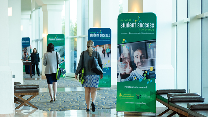 photo of attendees walking down hallway with conference banners