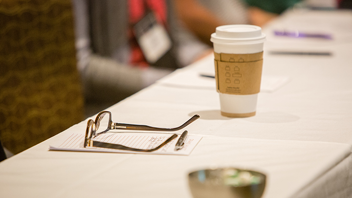 photo of conference table with glasses, notepad, pen and coffee