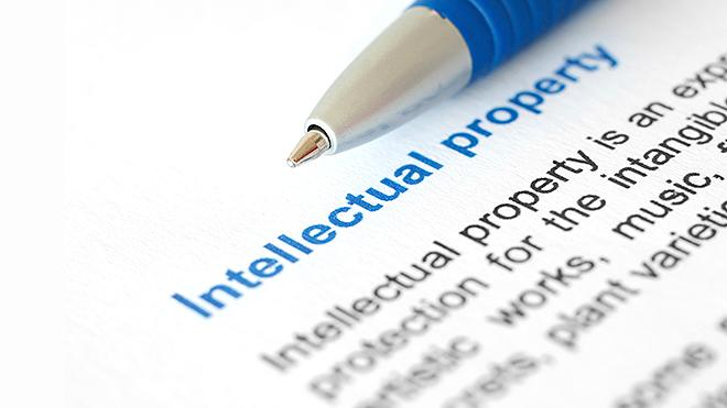 "Picture of a paper with ""Intellectual Property"" written in blue with a blue pen laying next to it."