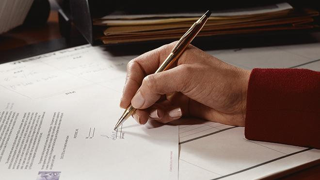 A hand holding a pen filling out a form with a signature.