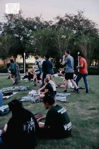 Students watching movies on the lawn