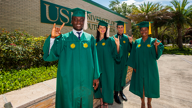 USF grads at commencement smiling and receiving diplomas