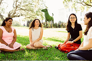 4 USF students sitting on ground Tampa campus