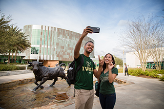 Two students taking a selfie in front of the USF Marshall Student Center on the Tampa, Florida campus.