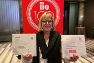 Amanda Maurer, Director Education Abroad. She has short blonde hair and is holding two awards presented to her by the International Institute of Education.