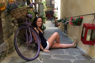 International Travel For Students. The picture shows a woman student sitting by a purple bike with a basket in an alleyway in Italy.