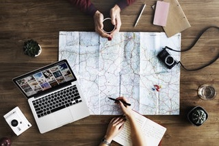 Useful Travel Information | Two people gathered around a map on a table surrounded by an open laptop, a journal, a camera, a pen, paper, and other implements showing that planning an upcoming trip is occurring.