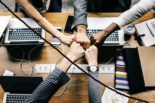 Online Resources | 5 people are pictured around a table with open laptops joining their fists together in a sign of solidarity and togetherness..