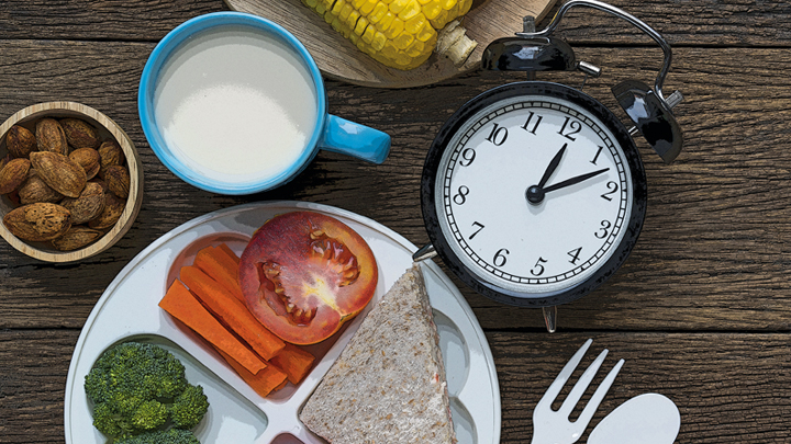 Picture of food with a clock laying on a table