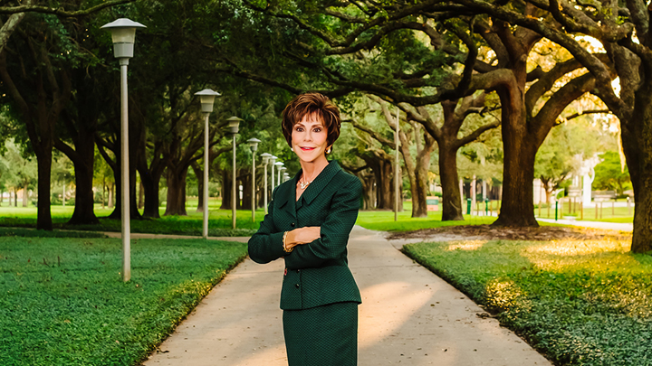 Judy Genshaft standing on campus in between trees