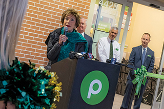 Judy Genshaft standing at a podium for the Publix grand opening