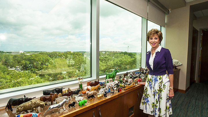 Judy standing by her desk with all of her bull statues
