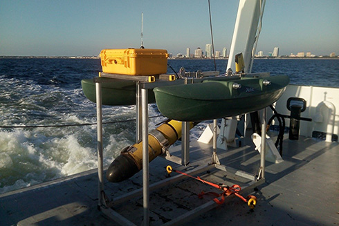 An autonomous underwater glider rests securely in its echosounder calibration float aboard the deck of the R/V Hogarth.