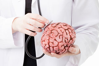 doctor holding a stethoscope to a brain